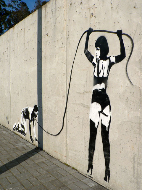 A spray painted black-and-white picture on a high concrete wall of a dominatrix leading someone by a leash