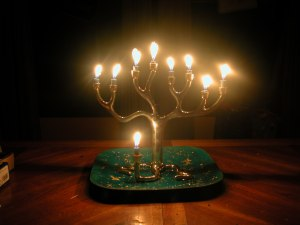 A silver menorah in the shape of a tree sits in a darkened room with all the holders filled with lit candles that are nearly burned to the end.