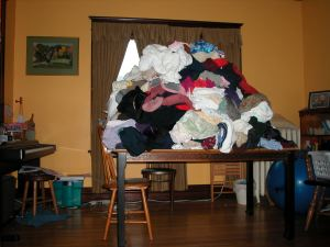 A dining room table piled several feet high in laundry.
